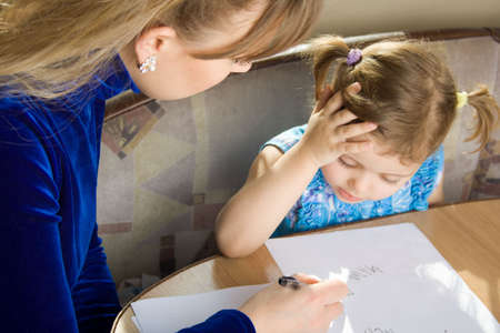 small girl learns to write, with mother cits at a table