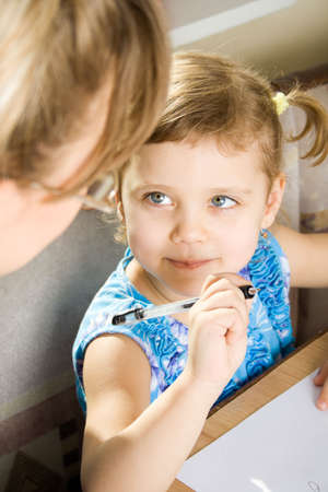 small girl learns to write, with mother sits at a table