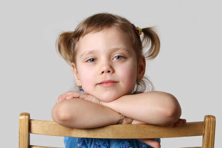 small girl sits on chair, gray background Stock Photo