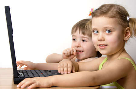 little girl and little boy working with a laptop