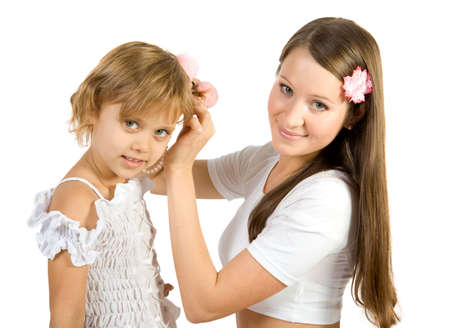 Young mother helps her daughter with her hairstyle. Isolate on white photo
