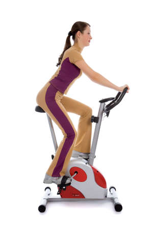 Attractive woman doing fitness on a stationary bike isolated on white photo
