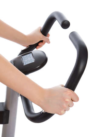 Woman hands on a bar stationary bike isolated on white photo