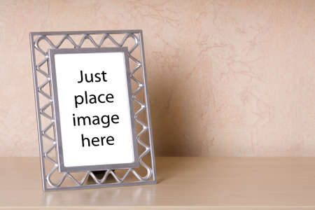Metallic photo frame on a wooden shelf Stock Photo