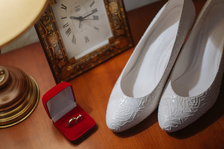 wedding vows: wedding rings in box on a nightstand with lamp and shoes Stock Photo