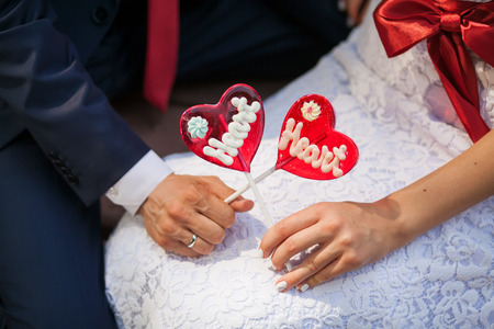 sugar veil: brides and groom hands holds heart shaped lollipop