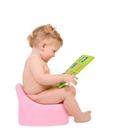 vasino: Pretty baby sedersi sulla rosa potty cifre e guardare al giocattolo. Isolato su bianco