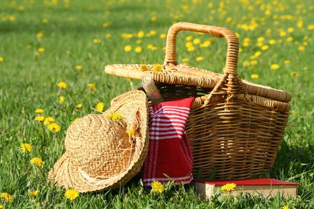 Picnic basket and straw hay laying on the grass photo