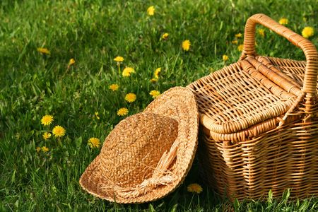 Summer hat and wicker basket on the grass photo