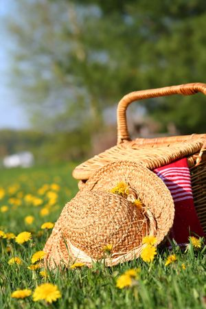 A picnic on the grass with wicker basket and sun hat photo