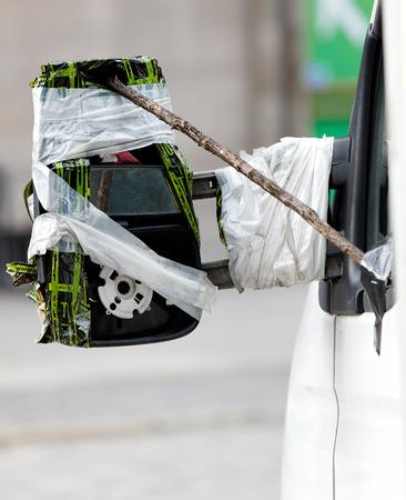 broken car: Funny way of repairing broken mirrow Stock Photo