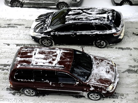 Snow covered cars on street photo