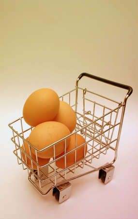 Minature shopping cart carrying brown eggs Stock Photo