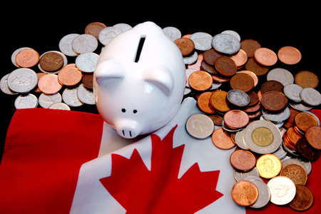 monies: Piggy bank and coins against Canadian flag