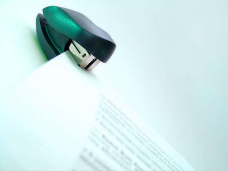 A mini stapler and a stack of papers with non-readable information on it.