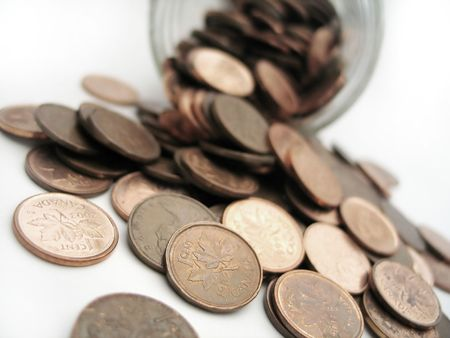 pennies: pennies spilling out of a glass jar
