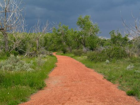 trailway: Red colored gravel path, surrounded by grass and trees, stormy skies in the background Stock Photo
