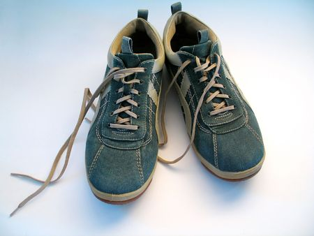 untied: A pair of sneakers. Focus on both sneakers. Shoelaces untied. Stock Photo