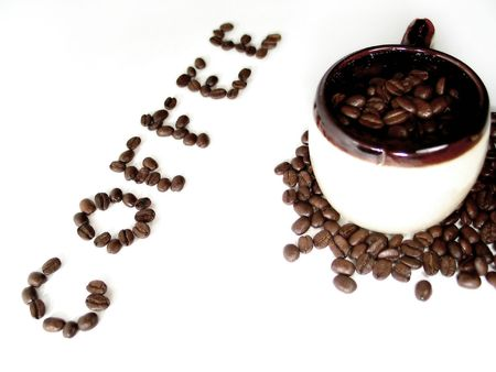 caffiene: A mug filled with coffee beans, the word coffee spelled out in beans next to it. Stock Photo