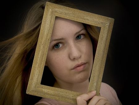 Woman holding an old picture frame over her face. Stock Photo