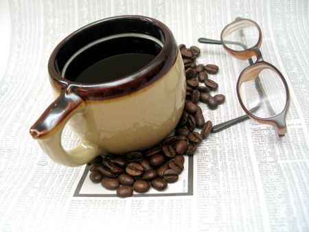 Coffee cup and beans and reading glasses sitting on the stocks section of the newspaper. Stock Photo