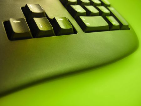 Bottom of a computer keyboard, focus on the arrow keys, with a bright green hue. Stock Photo