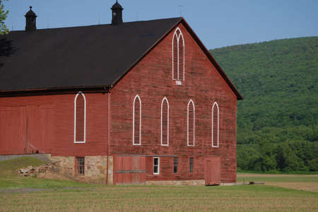 100 year old plus red farm bank barn surrounded by spring planting and mountains. Stock Photo - 961464