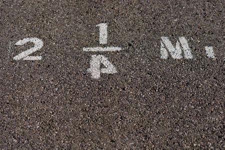 kilometraje: Mileage stenciled marcador en el pavimento con el numeral invertido cuatro.
