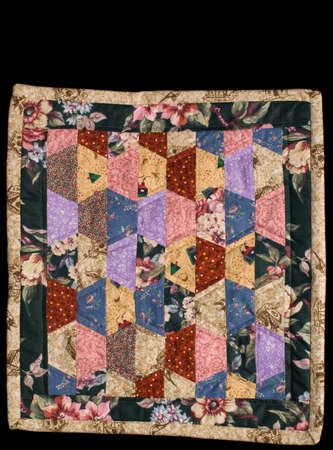 Tan quilt with pine tree figures on black isolation. photo