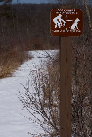 walking path: Dog cleanup sign on walking trail in winter.