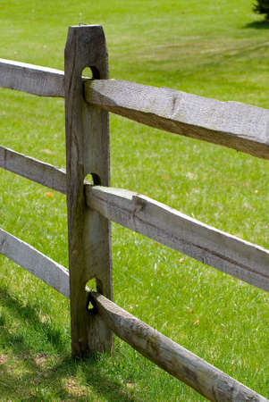Detail view of wooden split rail fence, lawn background.  photo