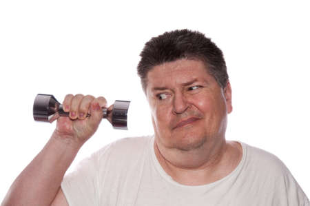 man working out: Middle-aged, overweight man struggles to lift a light weight dumbell. Stock Photo