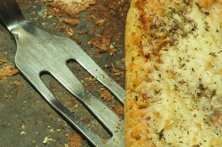 Closeup of grungy pizza pan, with pizza and serving utensil. photo
