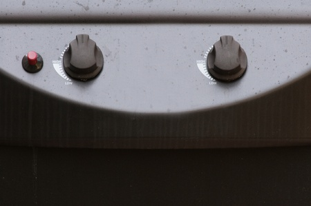 Closeup view of gas grill controls, with dials and a button. Stock Photo