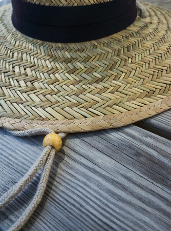 adjuster: Closeup of straw hat, with draw string and bead string adjuster.