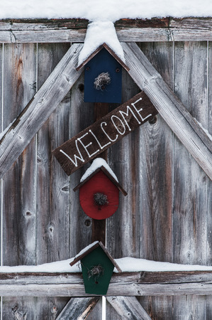 festooned: Residential welcome sign festooned with  some light snow hanging on a rough exterior fence gate.. Stock Photo