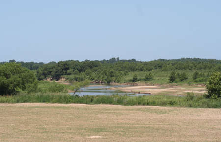 The Red River in the background of a field. Stock Photo
