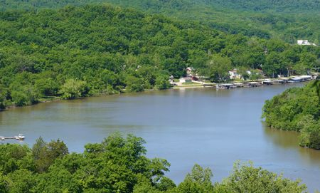 A great view of the lake of the ozarks showing some boat docks and the forrest