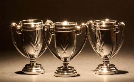 Three shiny trophies standing in a row.