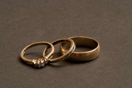 An engagement ring with a pair of wedding rings. photo