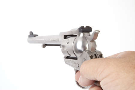 A hand holding a revolver, isolated. photo