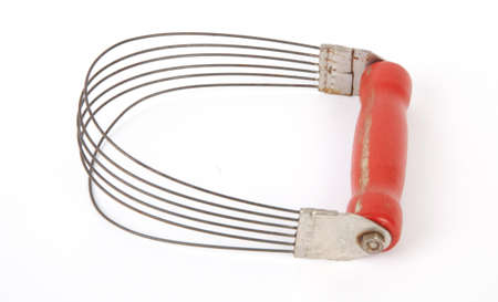 An antique pastry blender with a red handle, isolated.