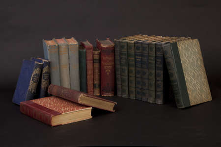 Row of old books on a black background.
