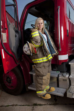 A female firefighter standing in the door of a fire truck. Stock Photo - 9909854