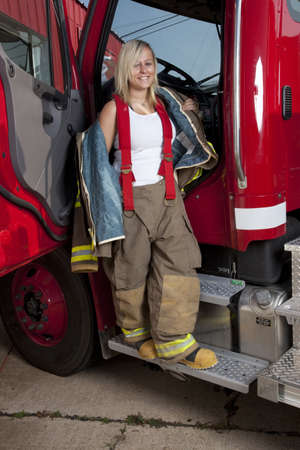 A female firefighter standing in the door of a fire truck. photo
