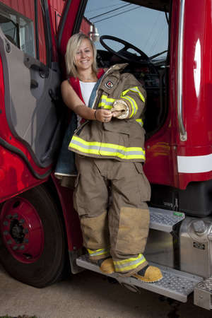engine fire: A female firefighter standing in the door of a fire truck. Stock Photo