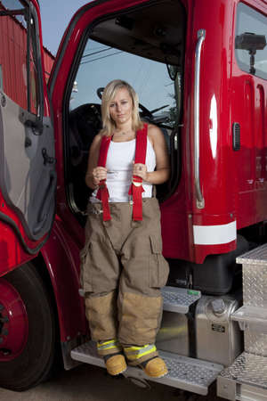 A female firefighter standing in the door of a fire truck. Stock Photo