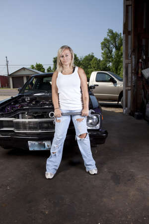 A female mechanic standing in front of a car holding a wrench. Stock Photo - 10205172