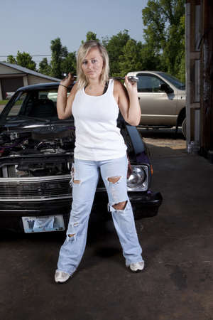 A female mechanic standing in front of a car holding a wrench. Stock Photo - 10205173