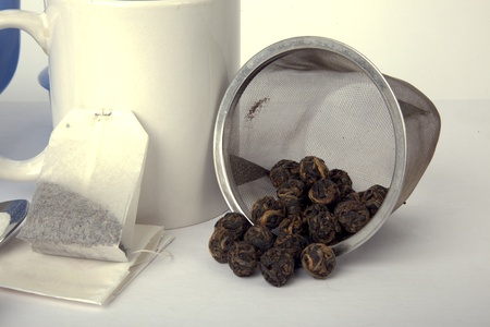 Tea balls, teabag, and a white mug. photo